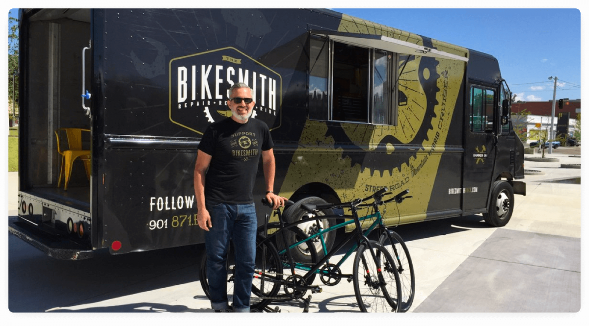 A picture of the founder of The Bikesmith, a mobile bike repair business, with his truck in the background.