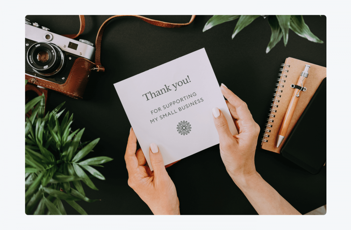 Female hands holding a card saying: Thank you! For supporting my small business